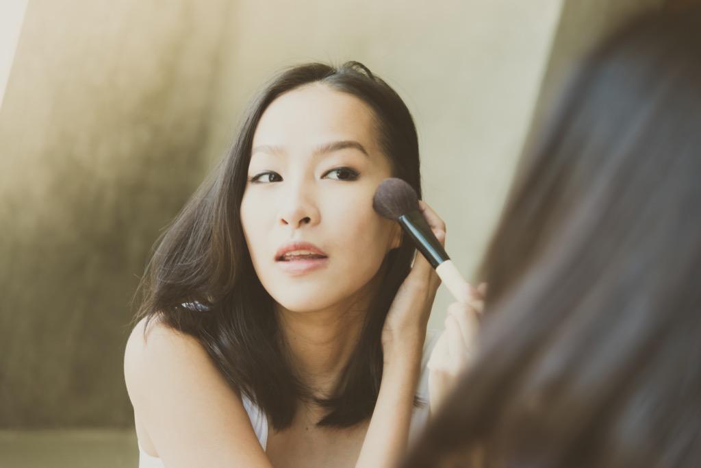 femme se maquillant dans un miroir, maquillage pour femmes plus âgées