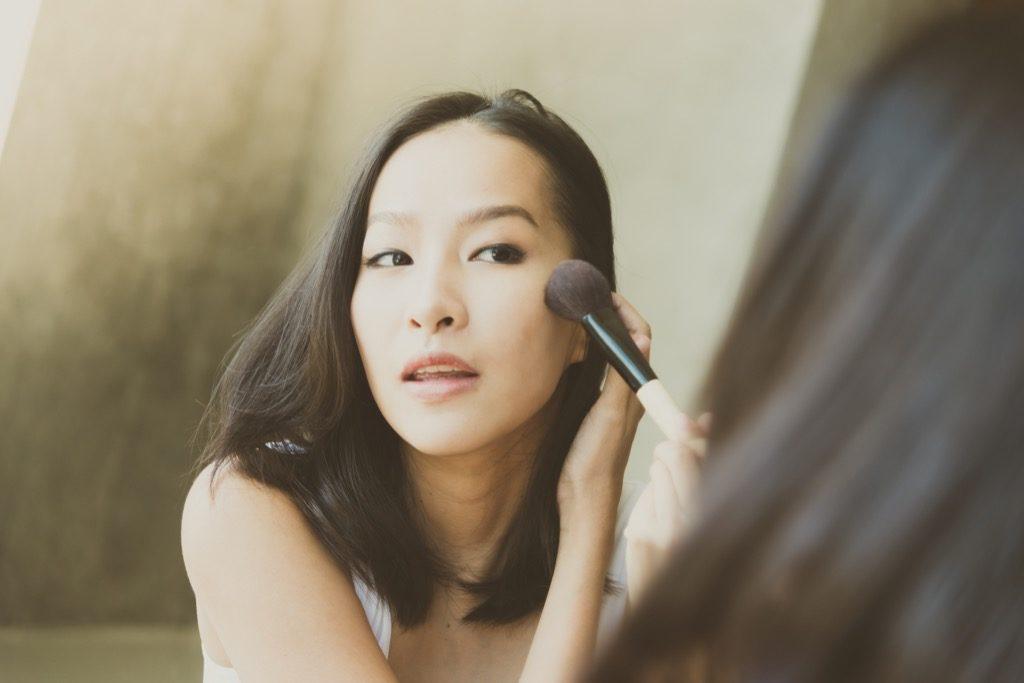 Femme se maquillant dans un miroir, maquillage pour femmes âgées.