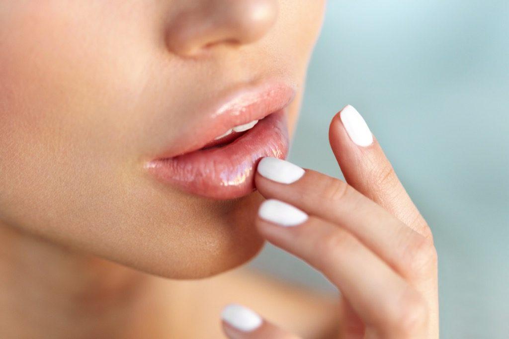 Femme touchant les lèvres, maquillage pour femmes âgées
