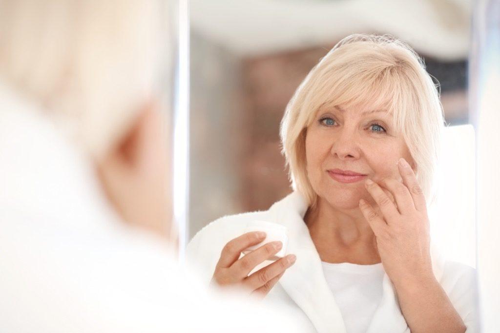 Femme d'âge moyen se regardant dans un miroir, maquillage pour femmes âgées.