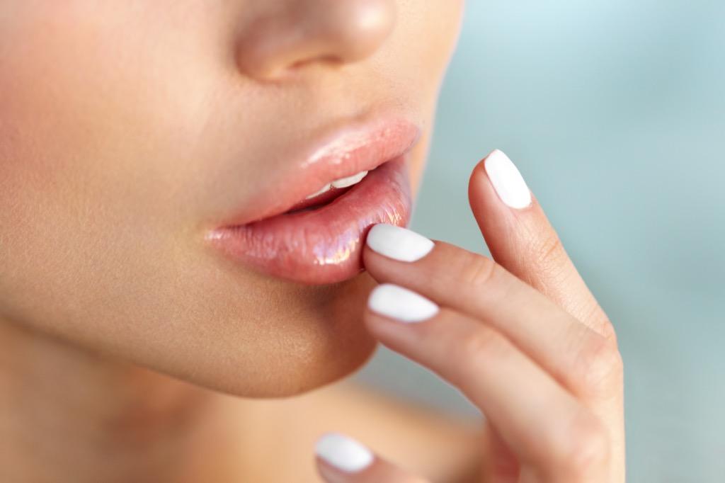 femme touchant les lèvres, maquillage pour les femmes plus âgées