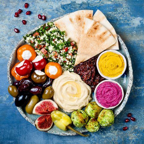 Plateau de meze du Moyen-Orient avec falafel vert, pita, tomates séchées, houmous de citrouille et de betterave, olives, poivrons farcis, taboulé, figues. Idée d'apéritif méditerranéen